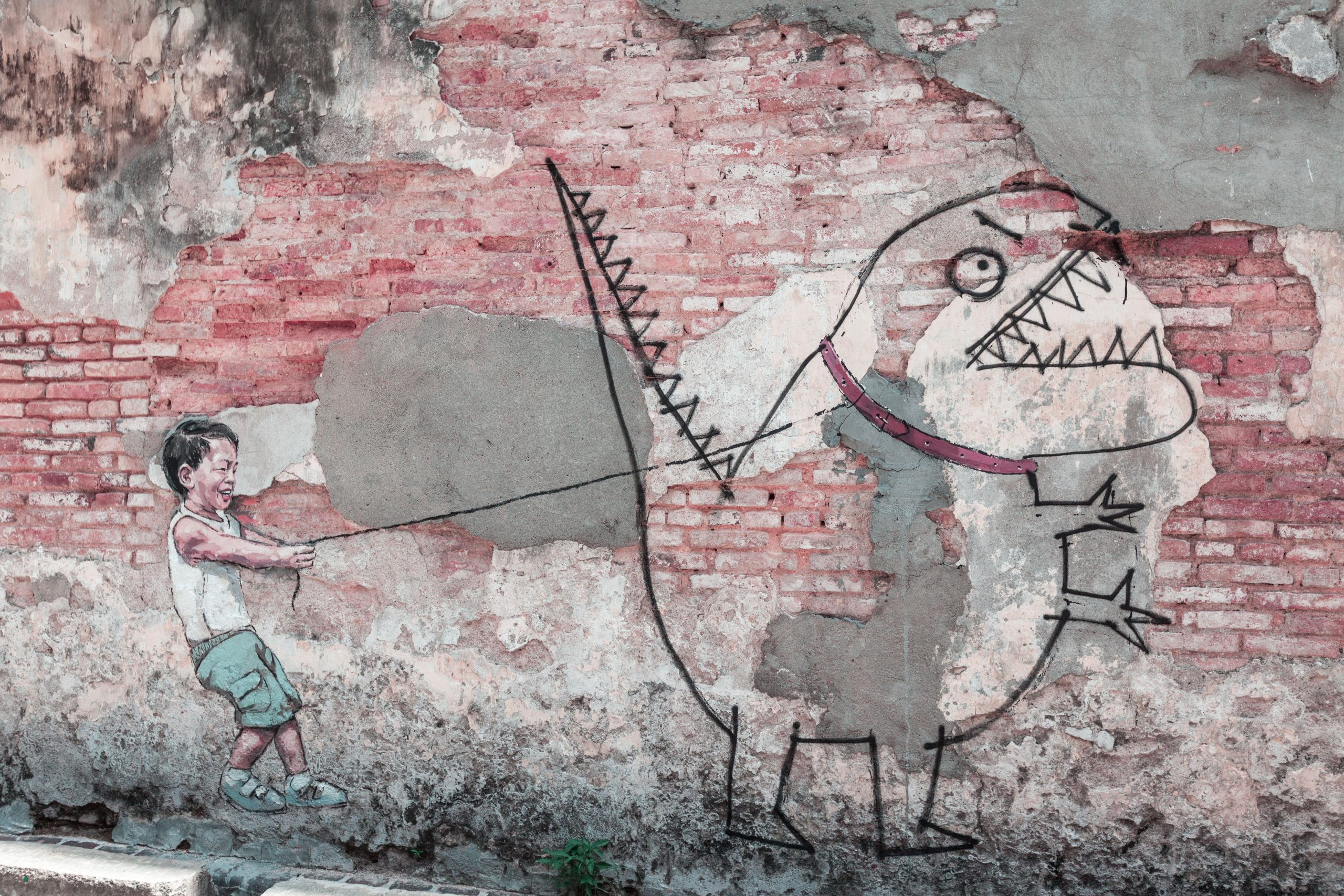 Graffiti image of a child with a monster on a leash.